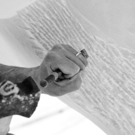 Sculptor carving marble with his tools