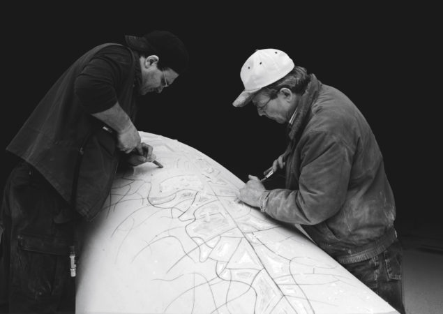 Two craftsmen installing a piece of marble.