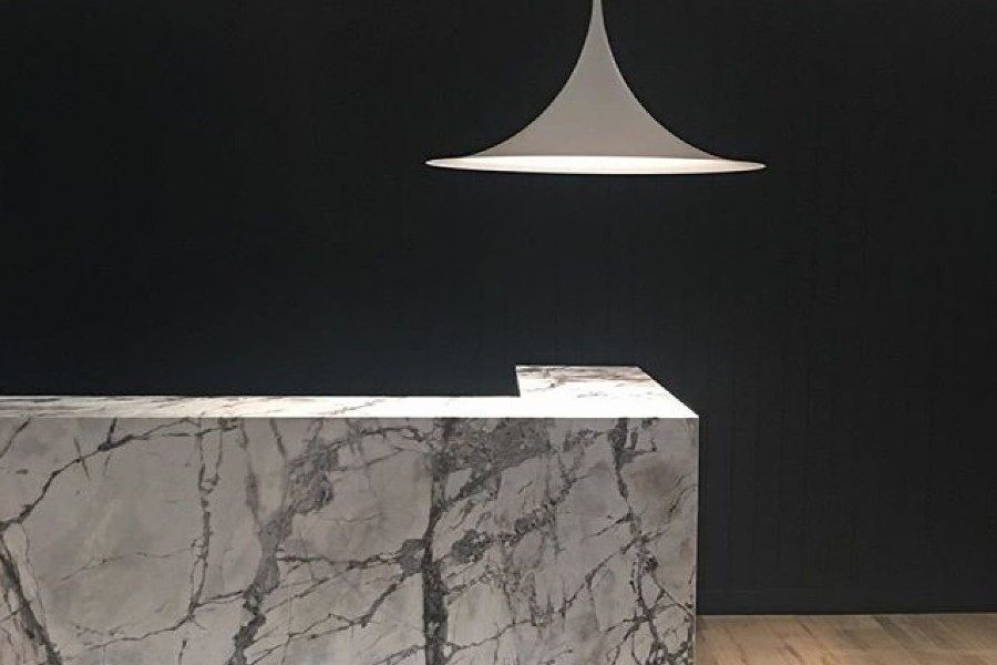 White marble reception desk with hanging lamp