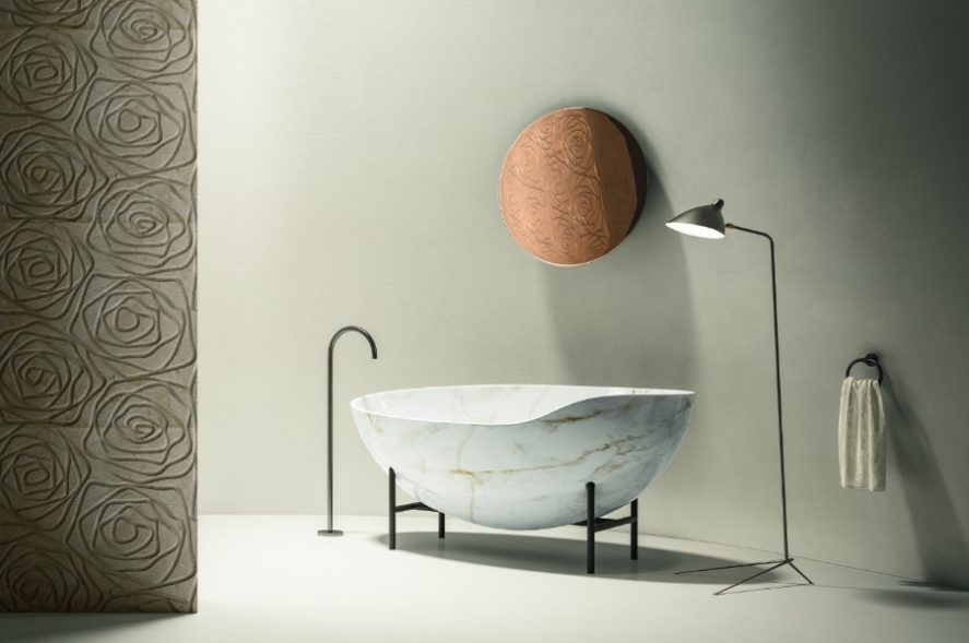 A luxury bathroom with Kora tub in white marble and stone tile walls