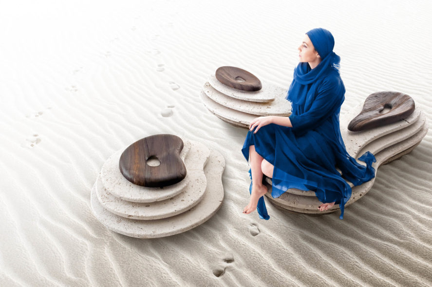 Woman sitting on Kreoo Oasi luxury stone seating