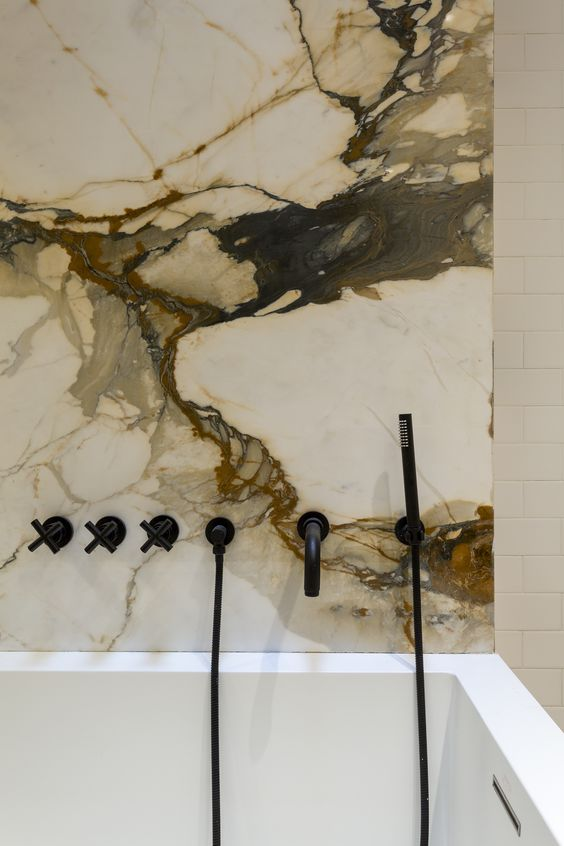 Black showerhead on white and brown marble wall