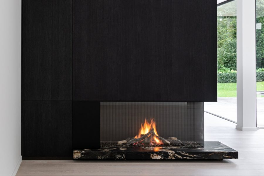 A minimialist, luxury black slate fireplace with black marble accents
