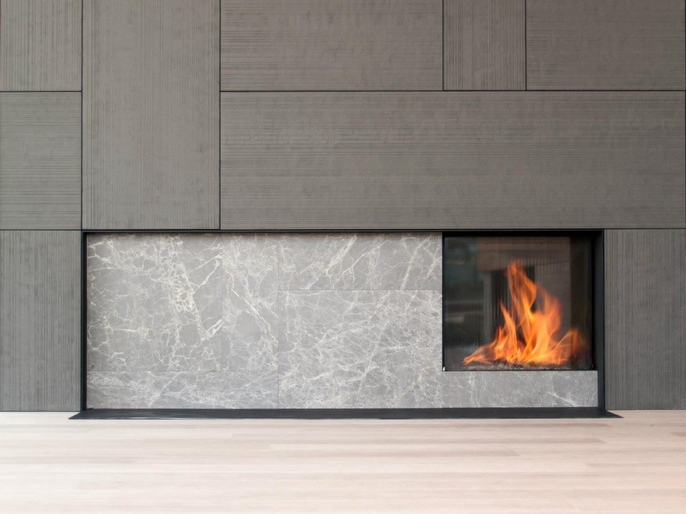 A grey marble luxury fireplace with roaring fire