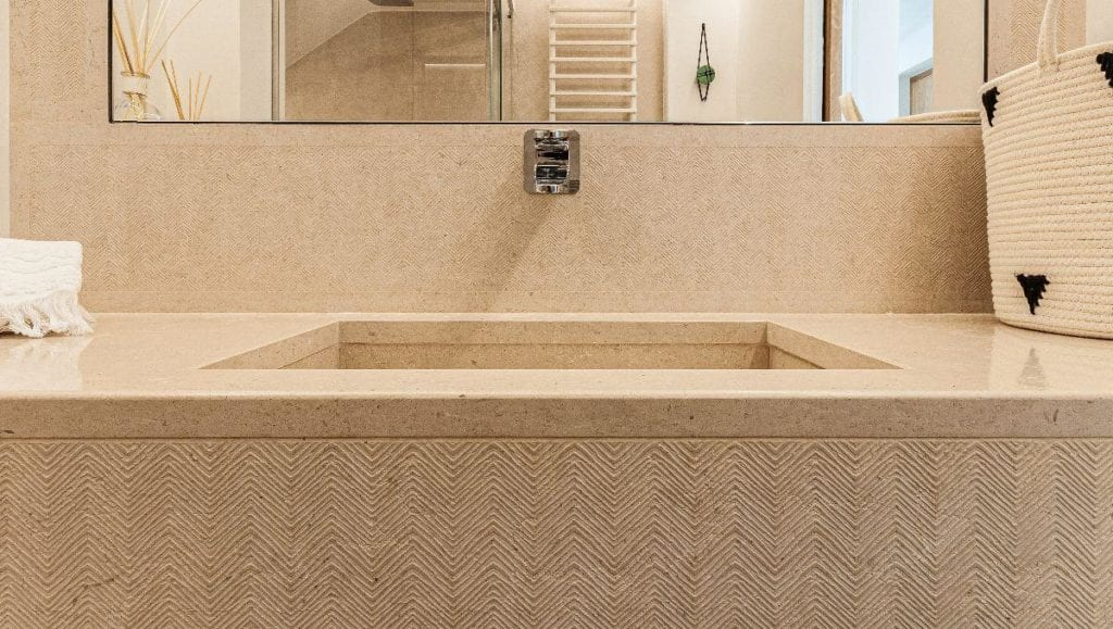 A stone bathtub with peach-colored textured wall tiles