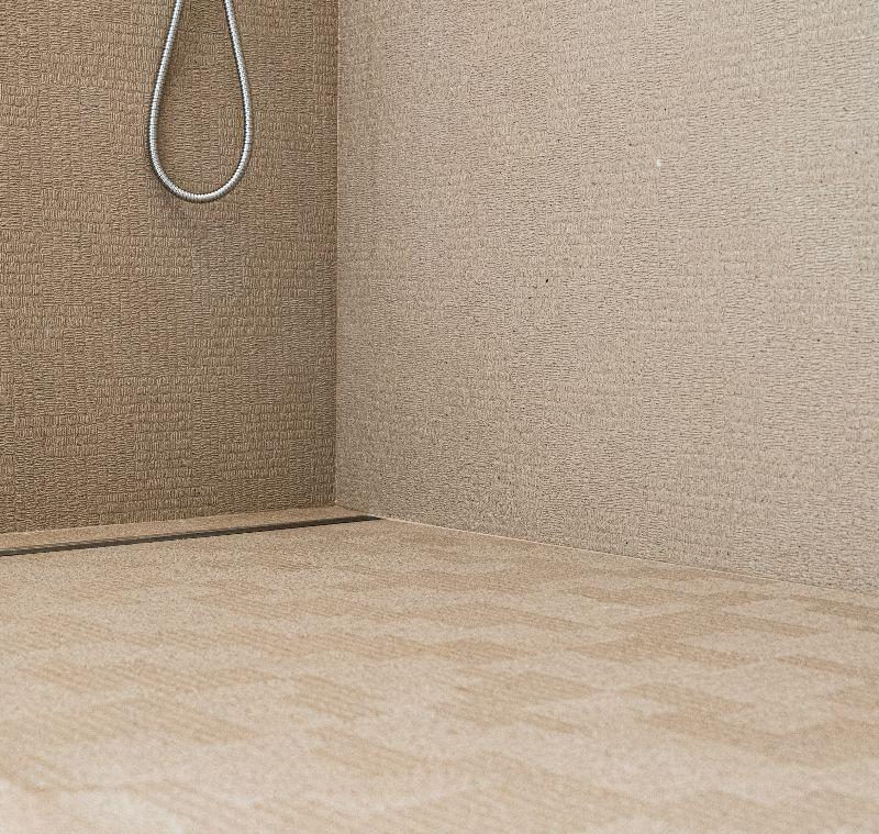 A luxury shower with beige textured wall and floor tiles