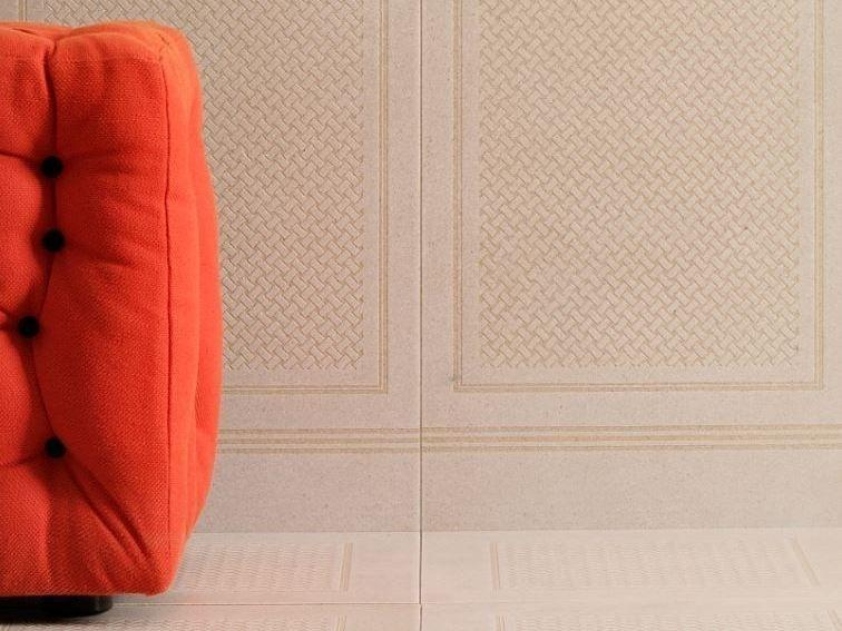 Finely textured stone wall tiles with an orange couch in front