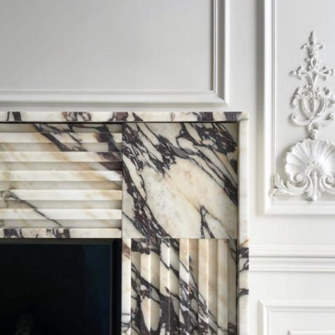 A fireplace mantel with textured marble around the edges